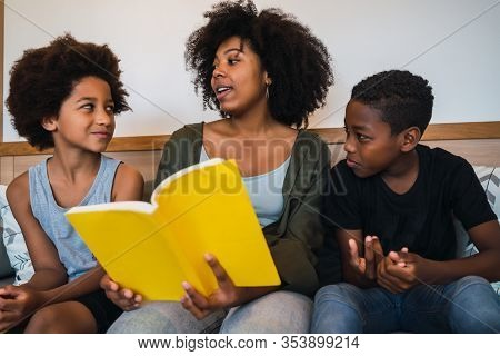 Portrait Of Afro American Mother Reading A Book To Her Children At Home. Family And Lifestyle Concep