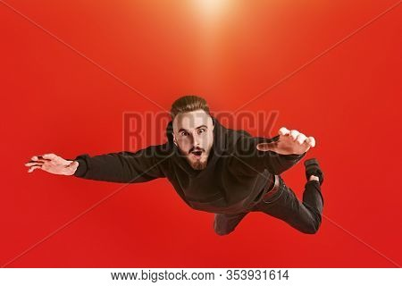 Excited young man is flying through the air like a superman. Studio portrait on a red background.
