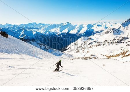 Skier Rides Down The Slope In Alps Mountains. Winter Sport. Val Thorens, 3 Valleys, France. Beautifu