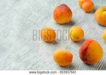 Several Apricots On White Wooden Background Close-up