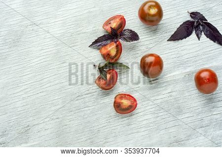 Various Colorful Tomatoes And Basil Leaves Over White Wooden Background. Top View, Flat Lay. Creativ