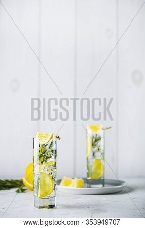 Two Glasses Of Refreshing Lemon Lime Drink With Ice Cubes In Glass Goblets Against A Light Gray Back