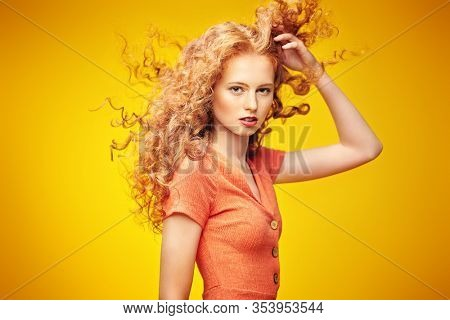 Long curly red hair. Portrait of a beautiful fashion girl with magnificent long hair in motion. Yellow background. Flying hair. Copy space.