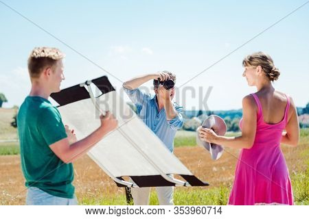 Photographer, model, and assistant working on set during a photo shoot