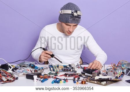 Close Up Portrait Of Young Pc Technician Working With Soldering Iron And Repairing Computer Motherbo