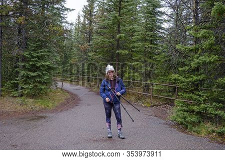 Young Woman On Her Way To Athabasca Falls, Tripod In Her Hands In The Rocky Mountains Of Canada