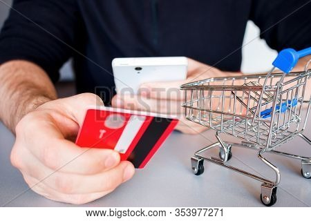 Man Holds Smartphone And Bank Card Close Up Online Shopping Concept