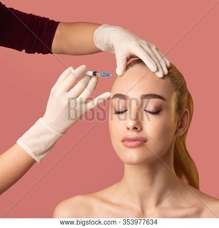 Face Skin Rejuvenation. Woman Getting Beauty Injection In Forehead Smoothing Facial Skin Over Pink S