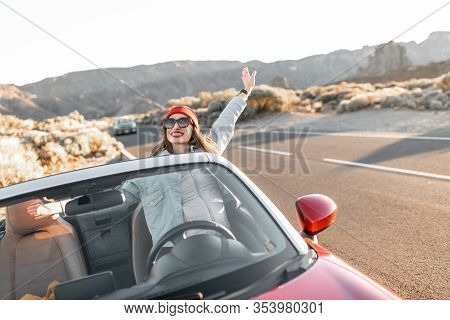 Lifestyle Portrait Of A Playful Woman Having Fun During A Road Trip, Raising Hands Out Of The Conver