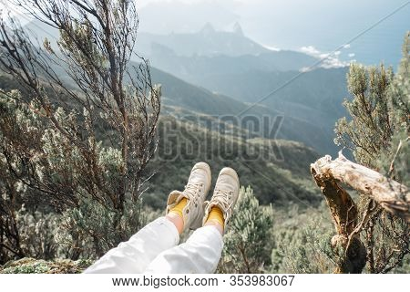 Woman Sitting Above The Precipice Highly In The Mountains With Great View On The Island, View On The
