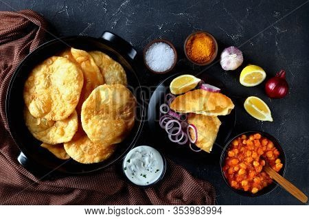Chole Bhature, A Popular Combo Of Puffed Fried Leavened Bread And Chickpea Curry On A Concrete Table