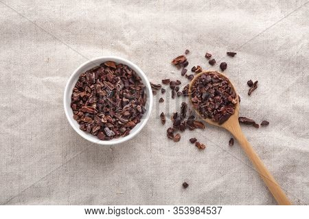 Cacao Nibs In White Bowl And Wooden Spoon On Table