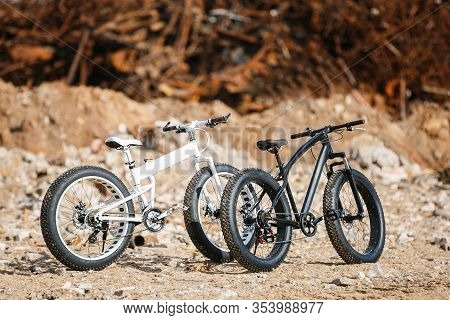 On The Street On The Stones Are Two Large Off-road Two-wheeled Bicycles With Male Fat Bike Frames. O