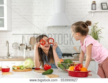 Mom And Daughter Prepare A Salad In The Kitchen.