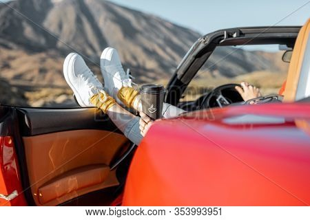 Woman Traveling By Convertible Car On The Desert Valley, Pulling Legs Out Of The Car Window On The R