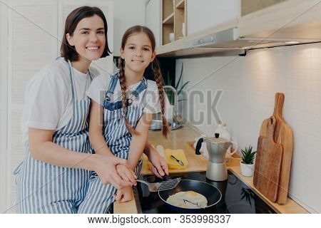 Pleased Mother With Little Helping Daughter Near Cooker, Prepare Breakfast For Whole Family, Fry Egg