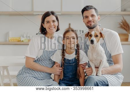 Family Portrait Of Father, Mother, Daughter And Pedigree Dog Pose Together For Making Memorable Phot