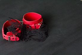 Red Leather Handcuffs, Erotic Black Mask On The Face On Black Background. Adult Games And Toys. Bdsm