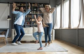 Overjoyed Three Family Generations Dancing At Home