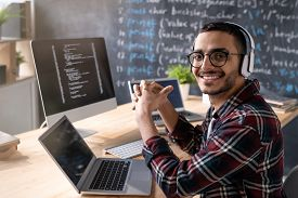 Young cheerful programmer with headphones looking at you with smile during work over new software in office