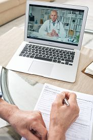 Medical specialist consulting senior man on health insurance claim online, unrecognizable senior man filling form while talking to doctor online