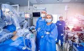 Hospital - Surgery Team In The Modern Operating Room Or Operating Theatre In A Clinic Operating A Pa