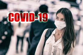 COVID-19 Novel Coronavirus virus infection spreading from Wuhan city, China. Asian woman wearing virus surgical face mask with text title. Chinese people walking to work at train station or airport.