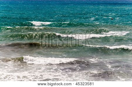 Rough sea with foamy waves and shades of blues and greens.