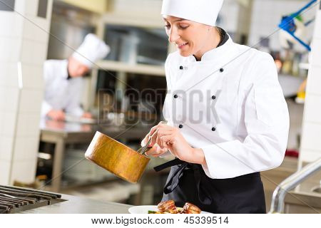 Female Chef in hotel or restaurant kitchen cooking, she is working on the sauce as saucier