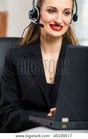 Young businesswoman or secretary working in her Office, she sitting in front of the window and working on a computer with a headset, she has a customer pitch