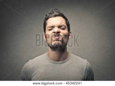 man portrait with a strange expression sniffing