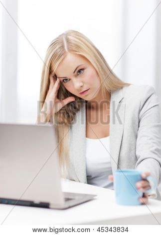 indoor picture of bored and tired woman with laptop