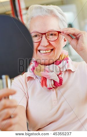 Nearsighted senior woman with new glasses looking into mirror at optician