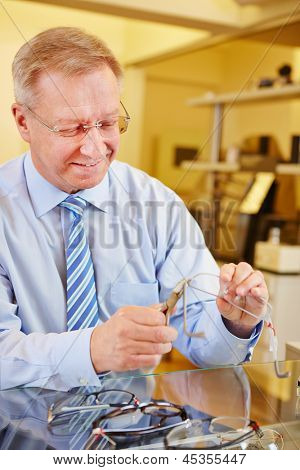 Elderly optician repairing glasses with bending pliers