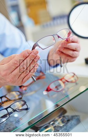 hands of an optician offering new glasses in his retail store