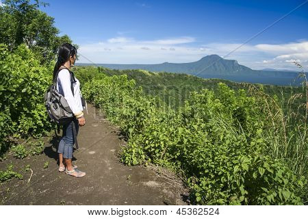 filipina girl looking at taal volcano crater lake from trail along rim near manila in the philippines poster