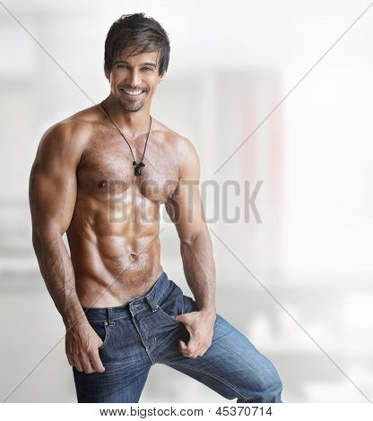Sexy smiling shirtless male model with muscular body and abs against white background