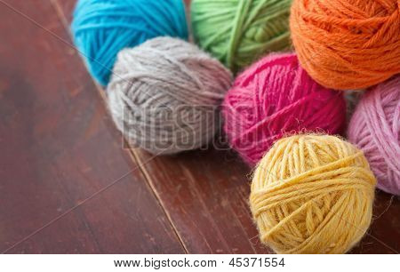 Balls Of Woolen Yarn On Old Wooden Background