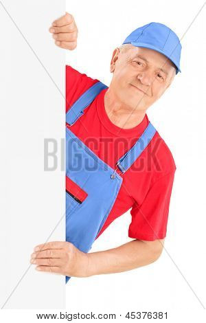 Mature repairman smiling and posing behind a blank panel, isolated against white background