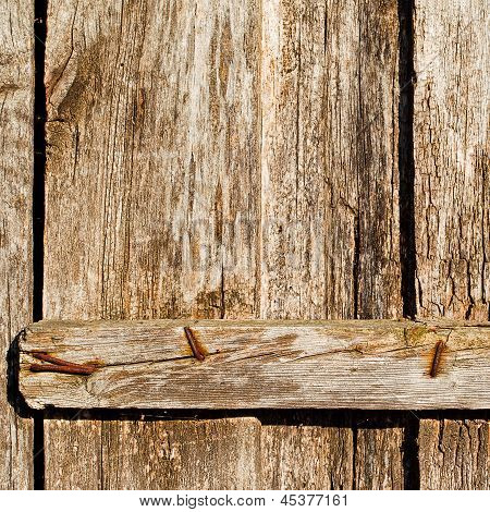 Old Used And Rusty Iron Nails On A Wooden Door
