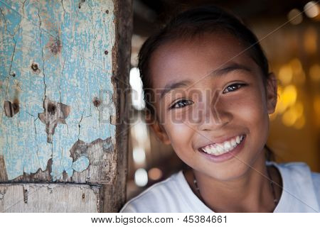 Portrait of a smiling Filipina girl from impoverished neighborhood in the Philippines.