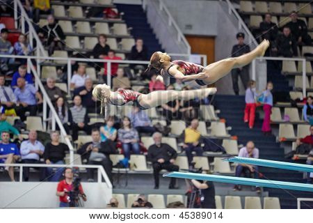 MOSCOW - APR 13: Female athletes perform exercise on syncronized springboard diving in Pool of SC O