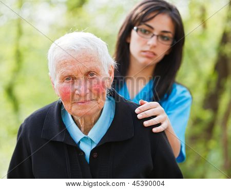 Sad elderly woman and caring nurse outdoors. poster