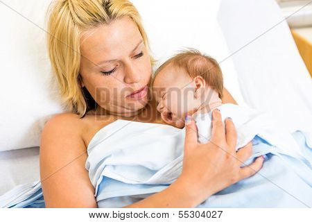 Loving young mother practising kangaroo mother care (skin to skni contact)