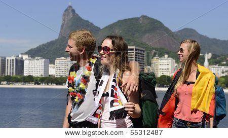 Group of German friends traveling at Rio de Janeiro holding Argentinian flag, with Christ Redeemer in the background.