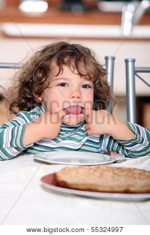 Toddler pulling a face at the table