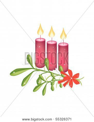 A Green Mistletoe And Three Christmas Candles