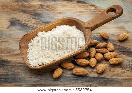 almond flour high in protein, low in carbohydrates, low in sugars and gluten free - a rustic wooden scoop on grained wood background
