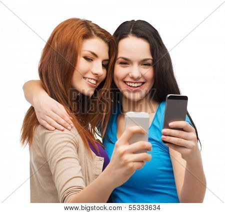 technology, friendship and people concept - two smiling teenagers with smartphones