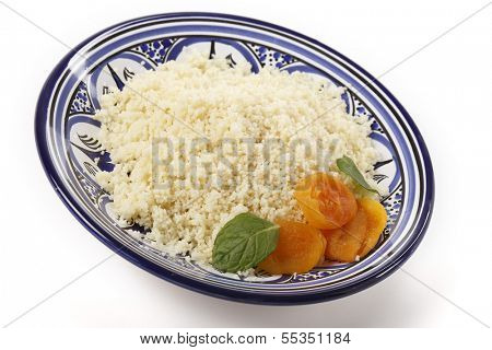 Plain couscous on a Tunisian handmade and hand-painted plate garnished with dried apricots and mint leaves